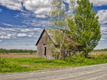 An abandoned barn in the road. This barn is in a country road near my home. I hope she has seen better days. Photo taken in summer 2017, Quebec, Canada Royalty Free Stock Photos