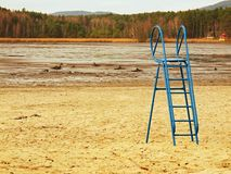Abandoned beach at empty pond with old blue kids slide  above muddy place and dirty beach sand. Autumn melancholic atmosphere. Stock Photos