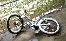 Abandoned bicycle in snow. Fallen down and abandoned bicycle covered with wet snow Royalty Free Stock Image