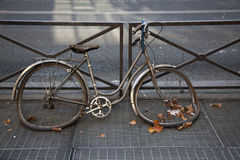 Abandoned bicycle on the street. Abandoned and heavily damaged bicycle locked on a fence Stock Photos