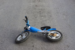 Abandoned bike on road. An old kids push bike is abandoned in the middle of the road Royalty Free Stock Photography