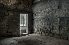 Abandoned Bluestone Prison Building Interior. Very old, dilapidated stone building interior in low natural light from an open doorway Royalty Free Stock Photo