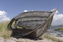 Abandoned boat. An old, broken, abandoned boat, lying in the grass on the rocks near the water Stock Photo