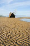 Abandoned boat. Derelict fishing boat abandoned on a sandy beach royalty free stock image