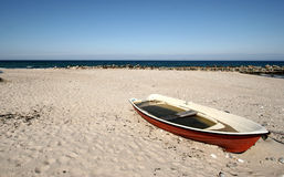 Abandoned boat on beach. Abandoned boat filled with water on sandy beach royalty free stock photos