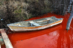 Abandoned boat in a contaminated red lake Stock Photos