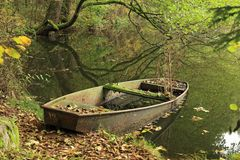 Abandoned boat on the forest pond Stock Photos