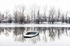 Abandoned boat in a frozen lake Stock Photography