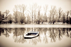 Abandoned boat in a frozen lake Stock Image