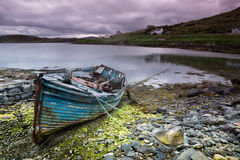 Abandoned boat on Isle of Lewis. Weathered fishing boat lying on a rocky beach on the Isle of Lewis, Outer Hebrides, Scotland royalty free stock photography