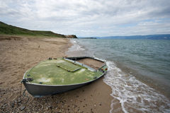 Abandoned boat on sand, Baikal lake coast, Olkhon. Royalty Free Stock Photo