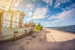 Abandoned boat on the sandy shore of a lake on a sunny day. distortion perspective fisheye lens royalty free stock image