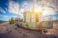 Abandoned boat on the sandy shore of a lake on a sunny day. distortion perspective fisheye lens. View stock images