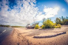 Abandoned boat on the sandy shore of a lake on a sunny day. distortion perspective fisheye lens stock photos