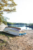 The abandoned boat. A small abandoned boat is laying upside down on a beach Royalty Free Stock Photography