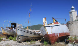 Abandoned boats. Lying on shore next to a lighthouse Stock Images