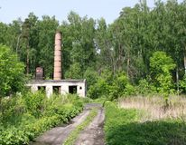 Abandoned boiler house. Dirt road to an old abandoned boiler house on the edge of the forest stock photos