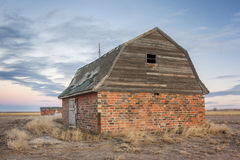 Abandoned brick barn. And farm buildings in eastern Colorado prairie at dusk royalty free stock image