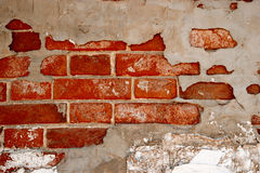Abandoned brick wall partially covered with gray cement plaster Stock Photography