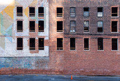 Abandoned bricks building in Detroit. Old abandoned building in the downtown of Detroit. Facade made of bricks, partly with a colorful painting. Broken windows royalty free stock photography