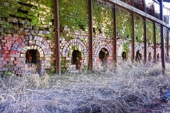 Abandoned brick kilns. Abandoned brickworks in Queensland Australia now overgrown with grass and moss.   Industrial heritage Royalty Free Stock Photography