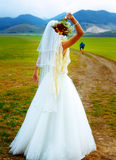 Abandoned bride and groom running away on a bike - funny wedding concept. Stock Photography