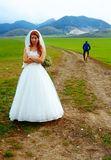 Abandoned bride and groom running away on a bike - funny wedding concept. Stock Photo