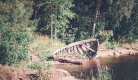 Abandoned broken boat on the river. Tinted photo. Old sunken fishing boat abandoned on the shore of the river. Tinted photo Stock Photography