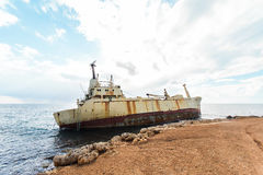 Abandoned broken ship-wreck beached on rocky sea shore. Royalty Free Stock Images