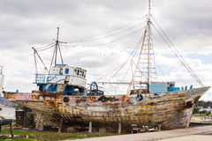 Abandoned broken ship-wreck beached on rocky sea shore. Royalty Free Stock Image