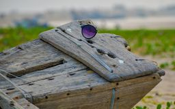 Abandoned and broken sunglass on a wooden structure. royalty free stock photo
