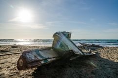 Abandoned broken wooden boat or pirogue with painted eye in front at beach on sunny day, Casamance, Senegal, Africa Royalty Free Stock Photos