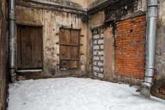 An abandoned building with boarded-up windows and doors in winter. An abandoned building with boarded-up windows and doors stock photos