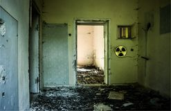 Abandoned building with broken glass and grunge walls because of nuclear accident. Radioative warning sign on the wall. Chernobyl stock photo