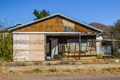 Abandoned Building In Desert. Old Abandoned Home With Boarded Up Windows In Disrepair & Located In Desert Royalty Free Stock Photo