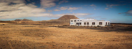 Abandoned building in dry landscape. Abandoned and broken white building in a dry, volcanic landscape Stock Images