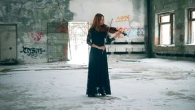 Abandoned building with a female violinist playing the instrument. 4K stock video footage