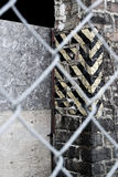 Abandoned building through fence. Detail of abandoned industrial structure viewed through a fence Royalty Free Stock Photography
