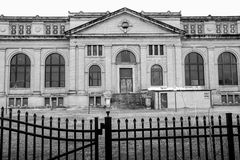 Abandoned Building. A large abandoned building sits behind a black fence in black and white Stock Photos