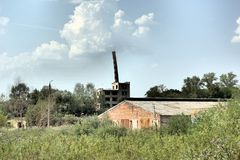 The abandoned building with mowned factory chimney Royalty Free Stock Photo