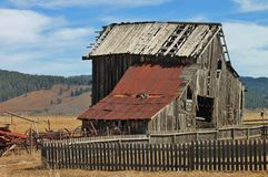 Abandoned building. Old abandoned barn surrounded by picket fence Royalty Free Stock Image