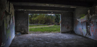 Abandoned building. Abandoned in space recreational area with graffiti burnt overlooking footbridge over river Stock Photos