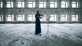 Abandoned building with a woman playing the violin. 4K stock footage