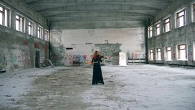 Abandoned building and a woman playing the violin in it. 4K stock video footage