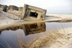 Abandoned bunker on beach. Scenic view of abandoned military bunker or pillbox on beach with sea in background Stock Image