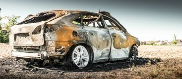 Abandoned burnt car at isolated field Royalty Free Stock Photo