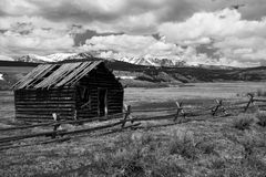 Abandoned cabin. Deserted house on a empty field, Rocky Mountains in the background Stock Image