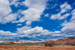 Abandoned Cabin. Small Abandoned Cabin In Vast Expanse of Hills and Mountains With Cloudy Blue Sky Royalty Free Stock Image