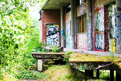 Abandoned campus restaurant being eaten by nature and grafitti. The street art and drug deal paradise Royalty Free Stock Images