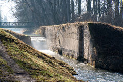 Abandoned canal lock. Abandoned and ruined canal lock on the Wiener Neustaedter Kanal in Austria with a spraying waterfall against the light Stock Images